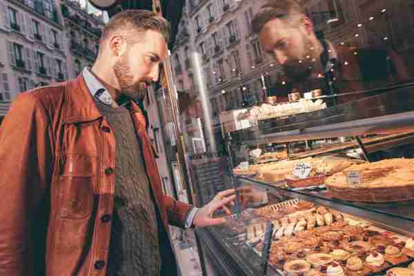 Young man choosing sweets in Paris, France