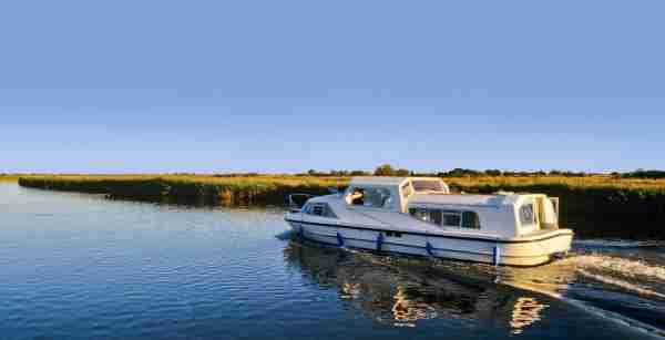 Cruising along on the Norfolk Broads (Photo by davidmartyn/Getty Images)