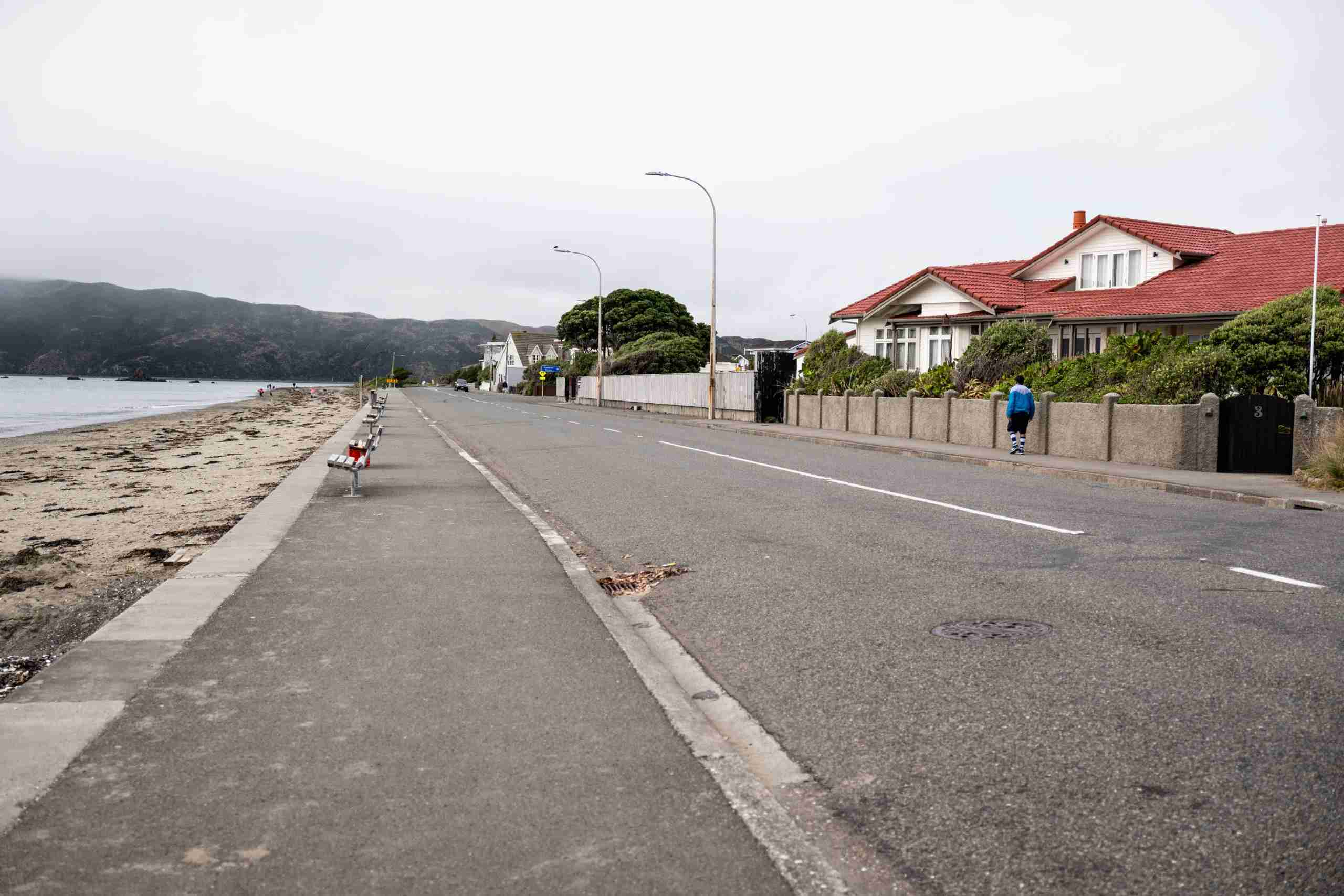 A pedestrian walks along an empty Marine Parade during a lockdown imposed due to the coronavirus in the Worser Bay area of Wellington, New Zealand, on Thursday, April 2, 2020. New Zealand