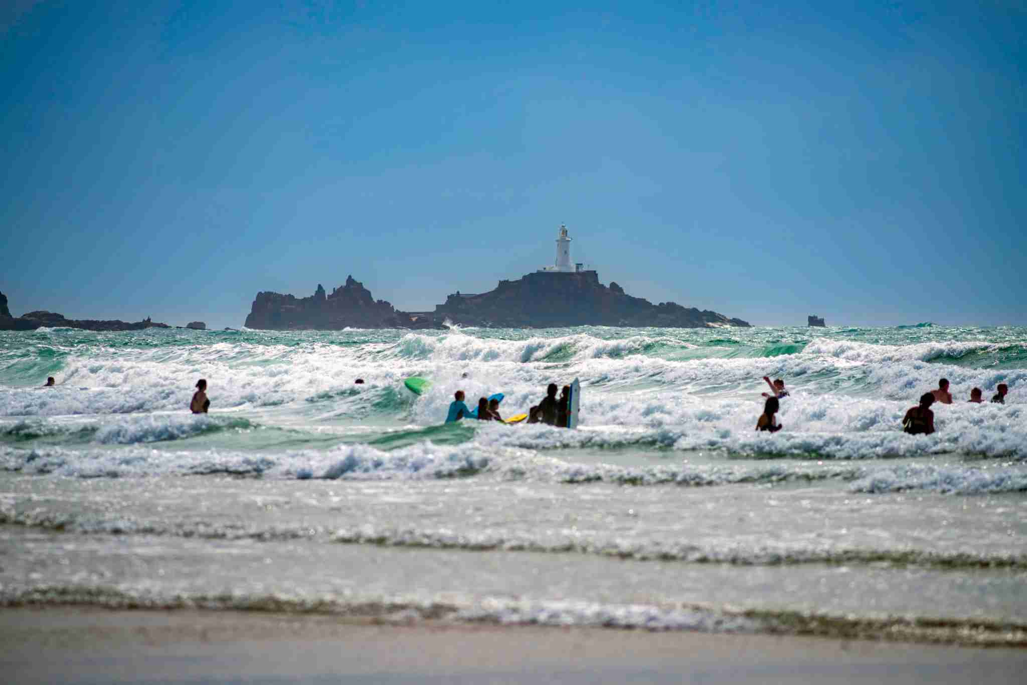 Silhouettes of surfers and swimmers, St. Ouen