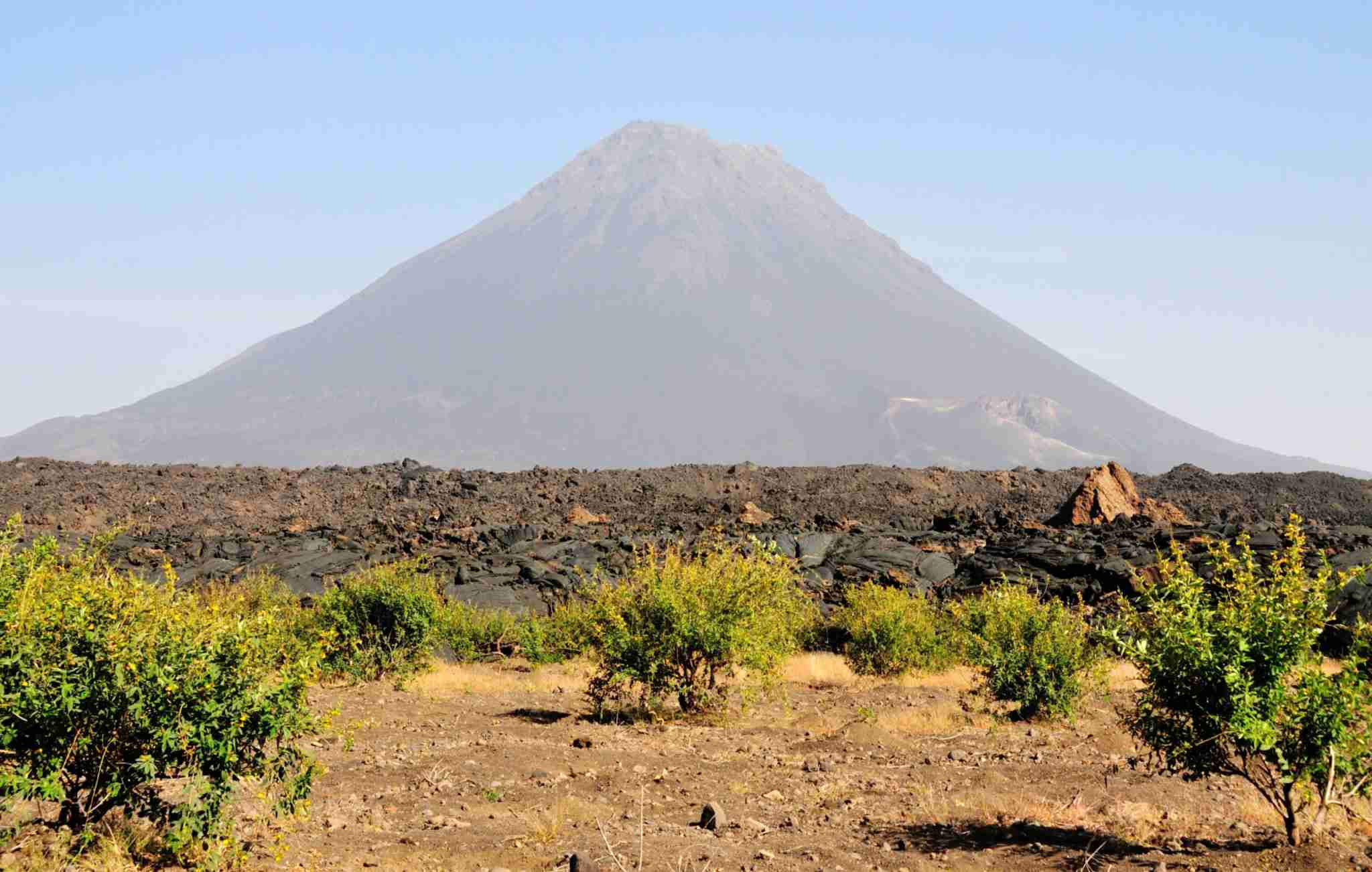 """Volcano """"Pico do Fogo"""" stands freely above the burned Lava fields and growing vegetation on the island of Fogo, Cabo Verde (Photo by Raularosa/Getty Images)"""