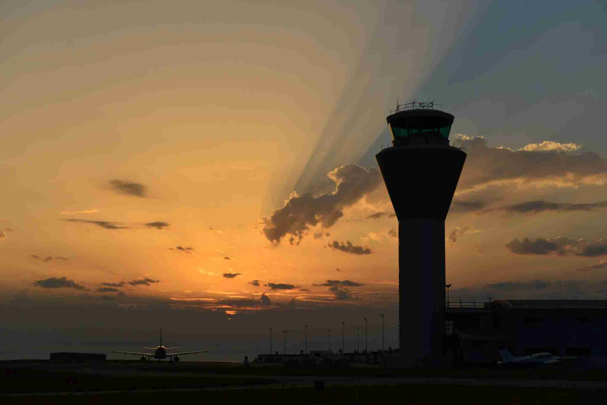 Airport control tower with a plane taxiing to the runway under a dramatic sunray sunset in the Summer. (Photo by Alan_Lagadu / Getty Images)