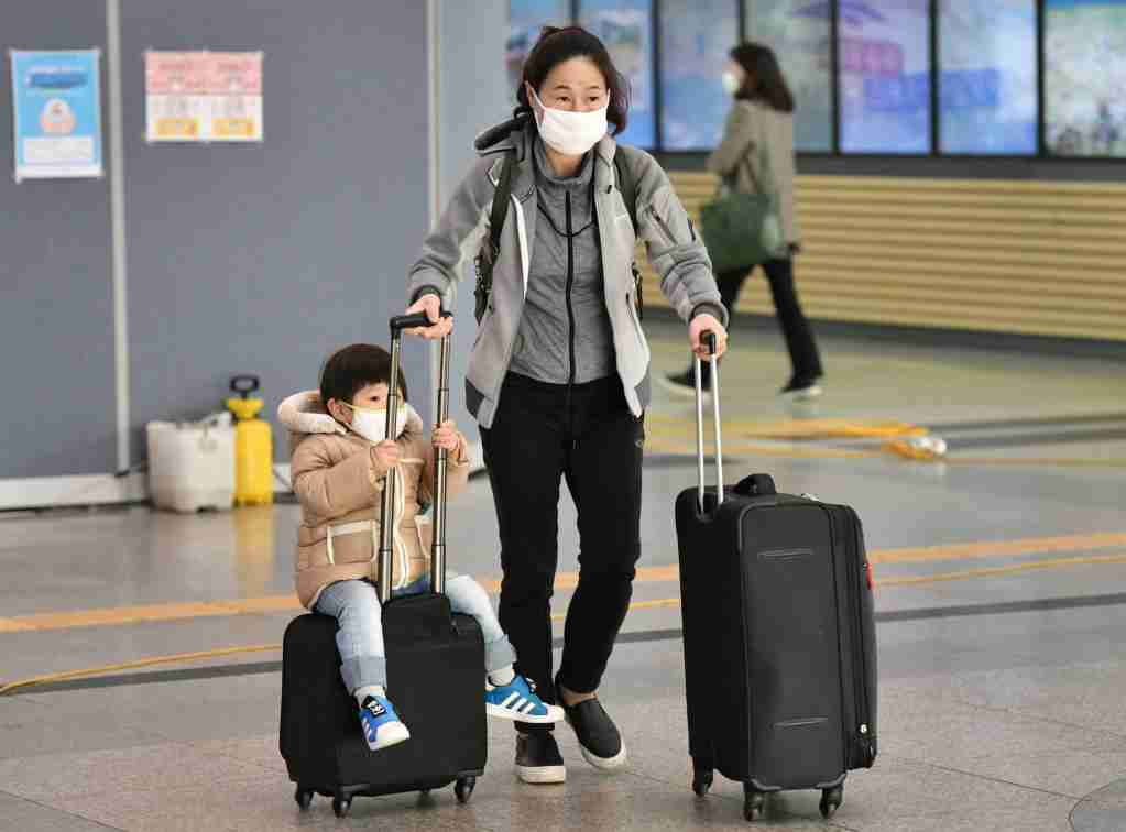 A boy wearing a face mask sits on a suitcase at a railway station in Daegu on February 26, 2020. - An American soldier stationed in South Korea has tested positive for the COVID-19 coronavirus, commanders said on February 26, as the country