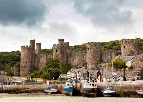 Conwy Castle and harbor at ebb-tide. Photo by eyewave / Getty Images