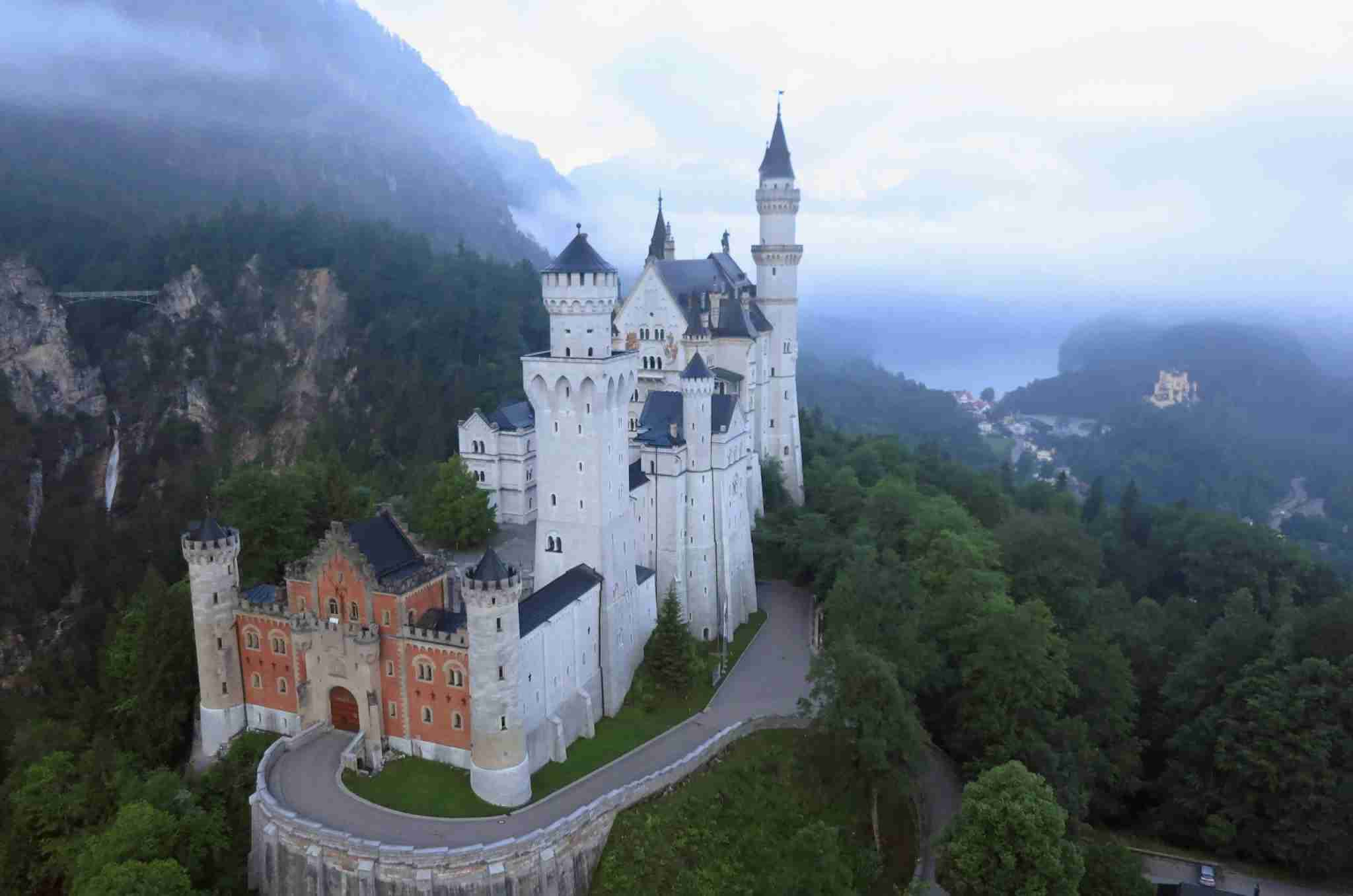 HOHENSCHWANGAU, GERMANY - JUNE 11: Schloss Neuschwanstein castle (L), as well as Schloss Hohenschwangau (R, in the distance), stand in this aerial view in the early morning on June 11, 2015 near Hohenschwangau, Germany. Schloss Neuschwanstein, built by Bavarian King Ludwig II, also known as Mad King Ludwig, is among Bavaria