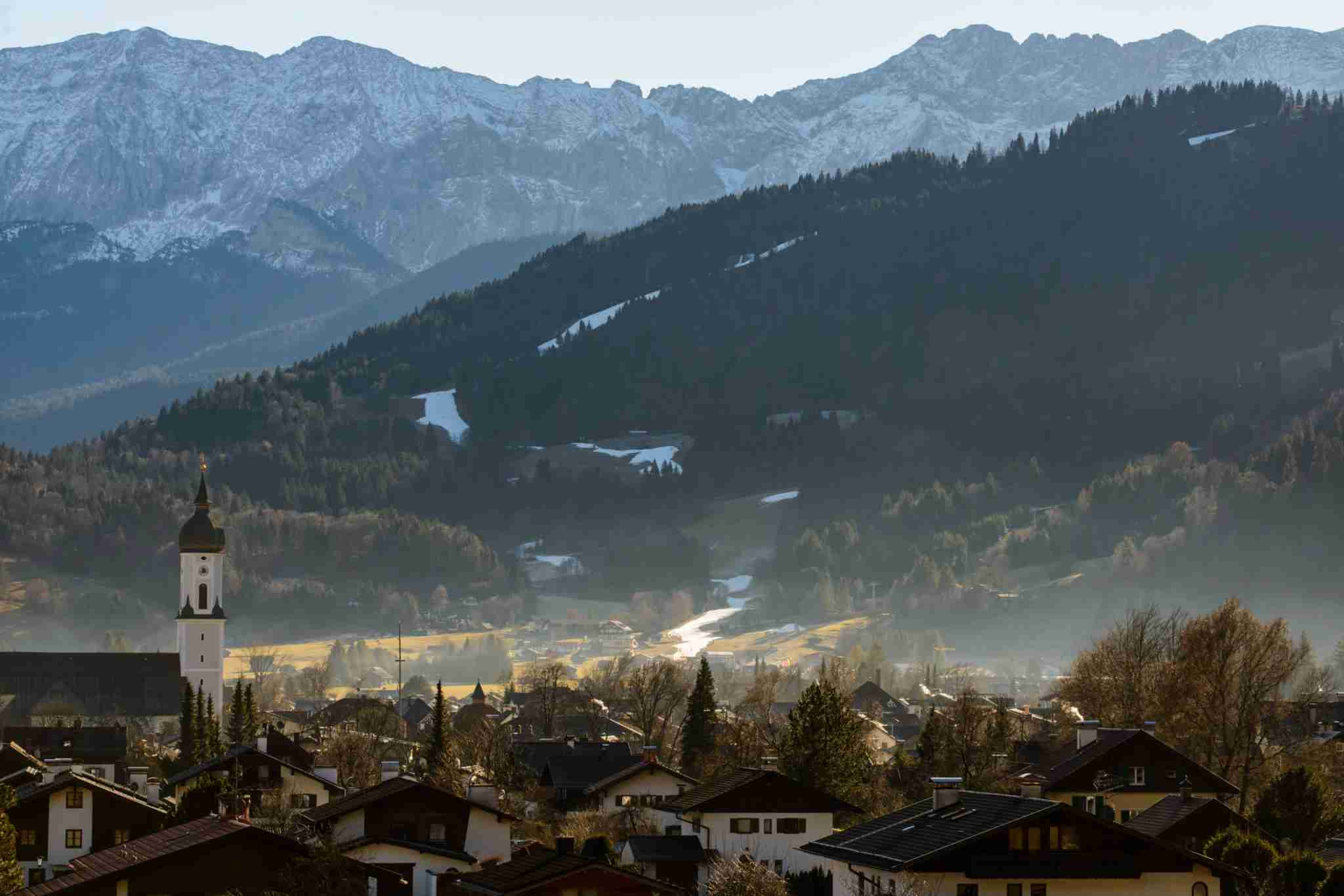 GARMISCH-PARTENKIRCHEN, GERMANY - DECEMBER 28: Patches of man-made snow cover the slopes of Garmisch Classic Ski area on a sunny day with temperatures of up to nine degrees Celsius in the German Alps on December 28, 2015 near Garmisch-Partenkirchen, Germany. Temperatures across Europe remain unseasonably high and many ski resorts at lower altitudes are facing a shortened ski season, if any season at all. (Photo by Philipp Guelland/Getty Images)