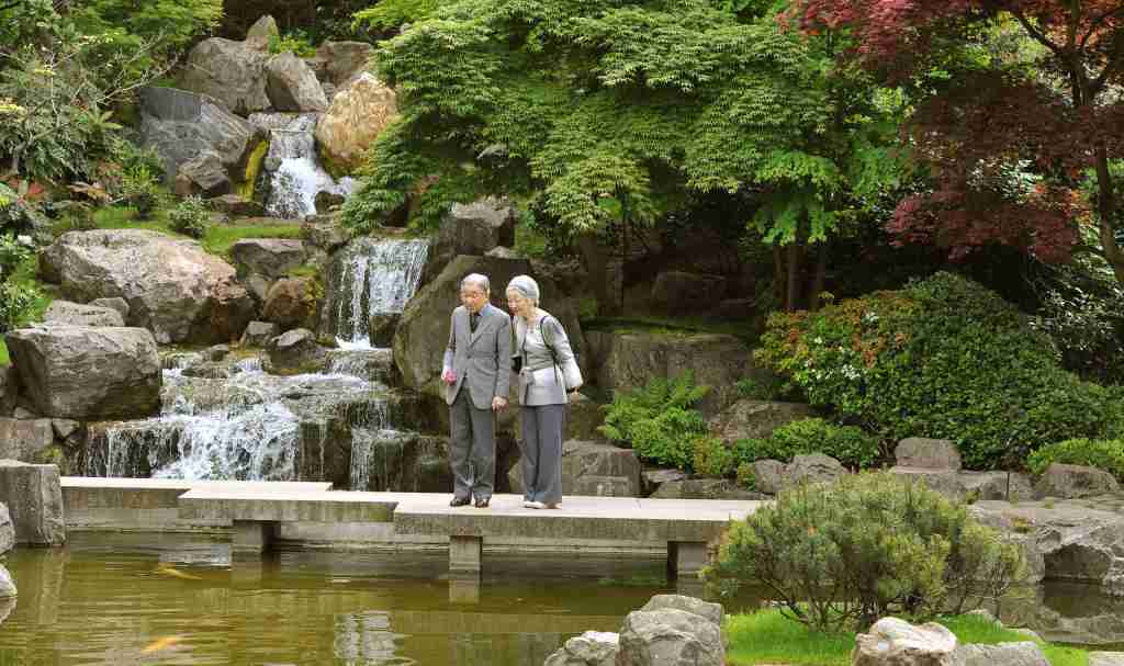 The Emperor and Empress of Japan Akihito and Michiko walk across a concrete bridge, as they tour the Kyoto Japanese Garden, in Holland Park West London. (Photo by John Stillwell/PA Images via Getty Images)