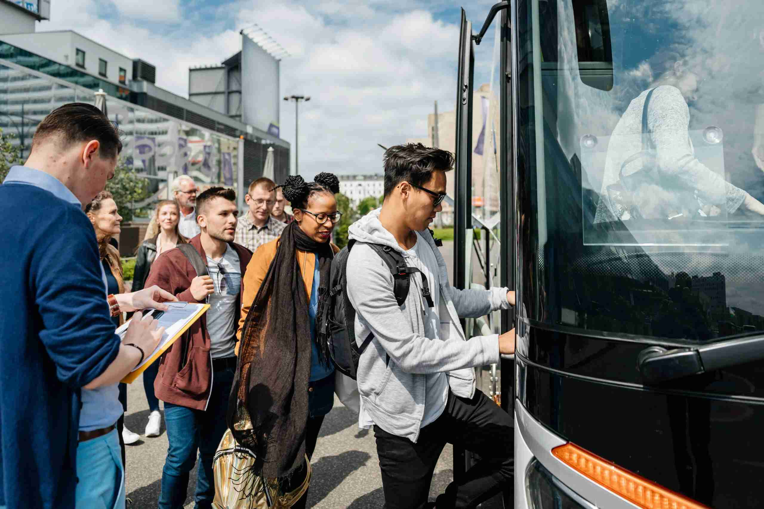 A bus is being boarded by a group of travellers, ready to begin their journey.