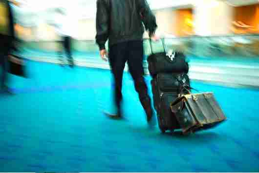 If you have more bags than you can carry on, you can often avoid fees by gate checking. Image courtesy of Shutterstock.