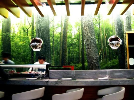 The forest backdrop and sushi bar at ATL's One Flew South