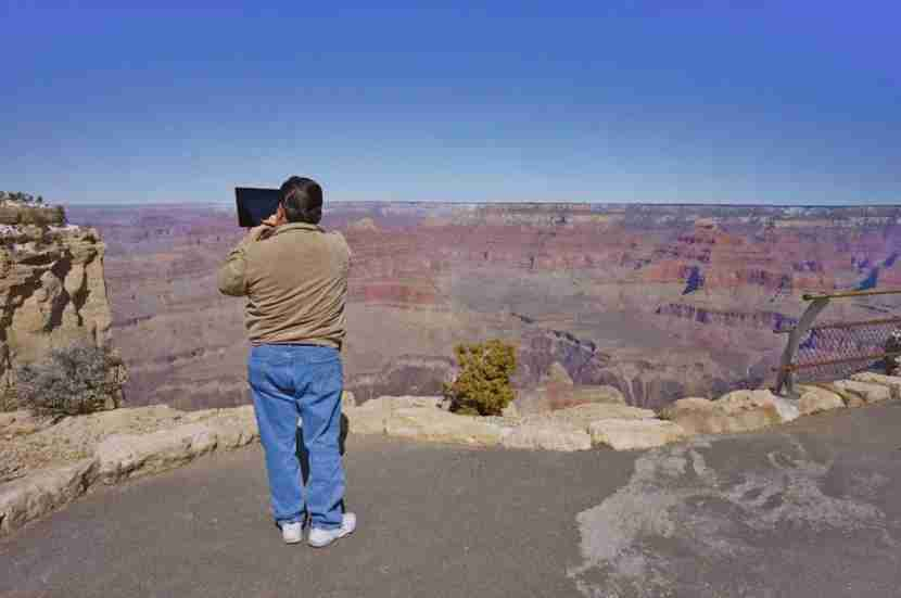 Taking a photo of the Grand Canyon with your iPad sure is funny—for people who see you do it. (Photo by Melanie Wynne/Have Snark, Will Travel)