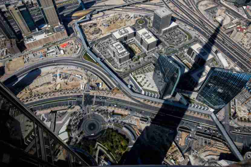 """The shadow of the Burj Khalifa is cast over the city of Dubai, as seen from the """"At The Top"""" experience of the Burj Khalifa on Tuesday, January 21, 2014 in Dubai, United Arab Emirates. If you want to save money, buy tour tickets a few days in advance, otherwise you"""