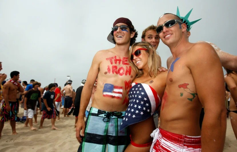 People pose for photos before the annual Iron Man competition on Saturday, July 4, 2009 in Hermosa Beach, Calif. Competitors haul themselves, flags, and beer into the air to celebrate Independence Day and show their patriotism as part of the Iron Man competition. In the Iron Man, a Hermosa Beach 4th of July tradition for 32 years, participants must run a mile, paddle board a mile, then chug a six-pack of beer, awards are given to those who do not puke Ð and those who puke the best. © 2009 Patrick T. Fallon