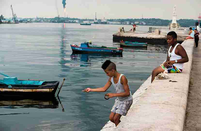 Boys handline fishing on Avenue Céspedes, where the Malecon continues along Old Havana. Photo by Mitch.