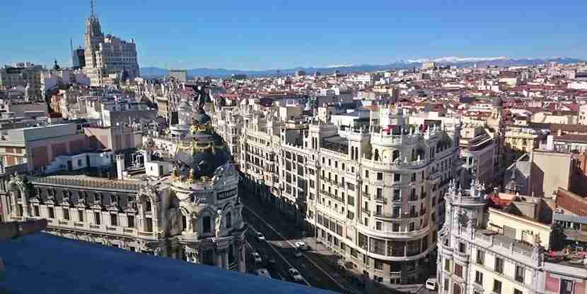 The Metropolis building, Calle Gran Via and the Sierra snow-capped mountains in the distance