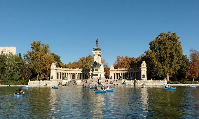Boaters enjoy the sunshine on a fall day in the Retiro park.