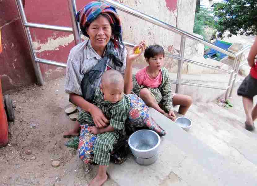 This mom in Myanmar sits with her children in hopes of getting some change.