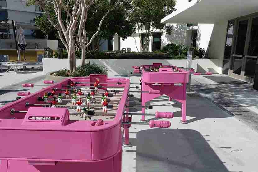 A pair of lonely bright pink foosball tables.