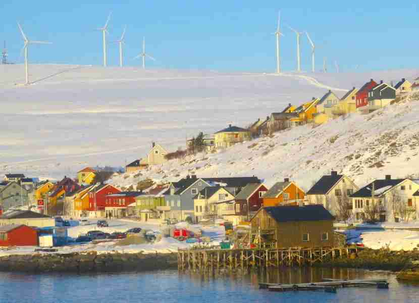 Beautifully colored houses set off the stark white polar landscape in Honningsvåg along with eco-friendly windmills.