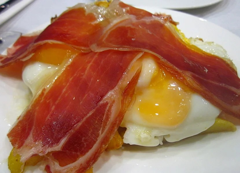 Broken eggs over potatoes topped with ham.