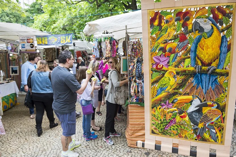 "Sunday at Ipanema's bustling Hippie Fair. Image courtesy of <a href=""http://www.shutterstock.com/pic-345994766/stock-photo-rio-de-janeiro-brazil-october-shoppers-look-at-art-displayed-at-the-outdoor-hippie.html?src=x7q8k9NwEEhJpDmeT3HTiA-1-2"" target=""_blank"">Shutterstock</a>."