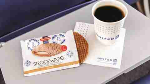 A stroopwafel snack and a cup of coffee on United Airlines