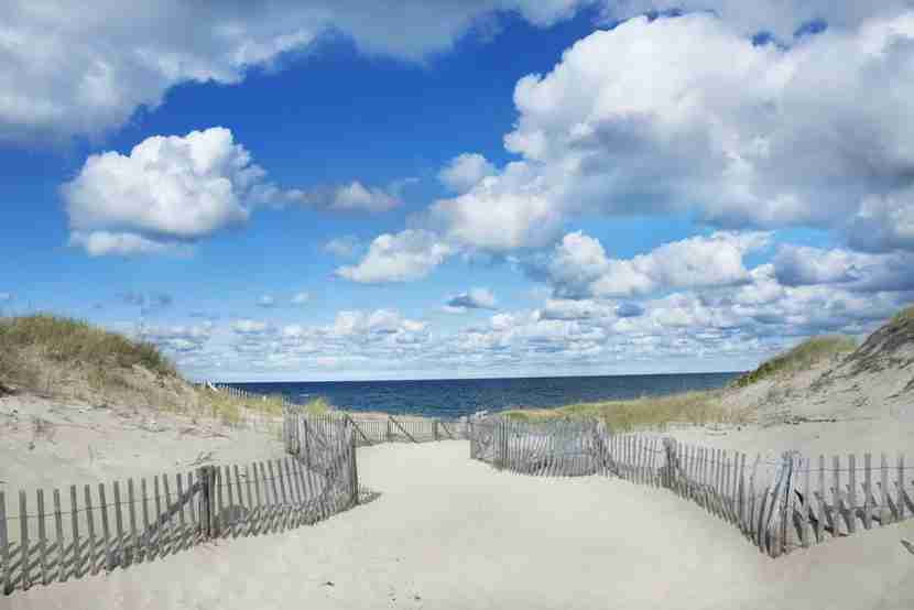 """A Cape Cod lighthouse. Image courtesy of<a href=""""http://www.shutterstock.com/pic-183901439/stock-photo-big-blue-sky-clouds-and-dunes-at-race-point-beach-on-cape-cod-provincetown-massachusetts.html?src=G723Z3vZlwQIebVwpuKeVA-1-3"""" target=""""_blank"""">Shutterstock</a>."""