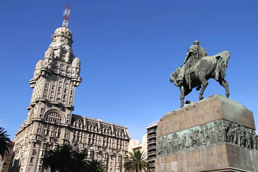 """Plaza Independencia in downtown Montevideo, Uruguay's capital city. Image Courtesy of <a href=""""http://www.shutterstock.com/pic-96006197/stock-photo-the-plaza-independencia-in-montevideo-uruguay-the-palacio-salvo-in-the-background-and-the-monument-of-the-grave-of-general-artigas-in-the-foreground.html?src=PuNIQU8HuogItk4MczRg6g-1-3"""">Shutterstock</a>."""
