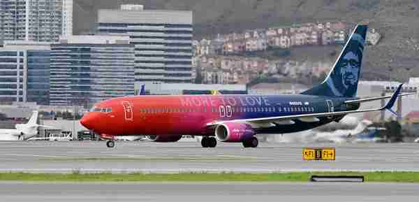"In this photo released by Alaska Airlines, A specially painted, co-branded Alaska Airlines and Virgin America 737-900ER aircraft, painted in shimmering red, purple and blue and featuring the slogan ""More to love,"" lands at San Francisco International Airport on December 14, 2016 in San Francisco, CA. The newly painted aircraft is part of the merger celebration of Alaska Airlines and Virgin America. (Photo by Alaska Airlines, Bob Riha, Jr.)"