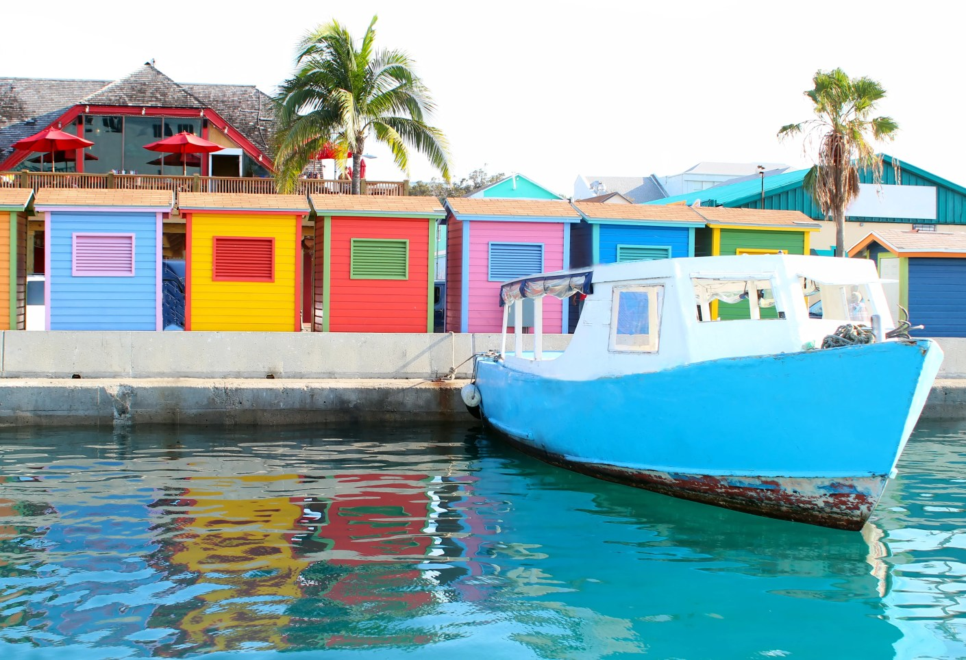 A colorful image of the waterfront area in downtown Nassau showing a water taxi and several huts.
