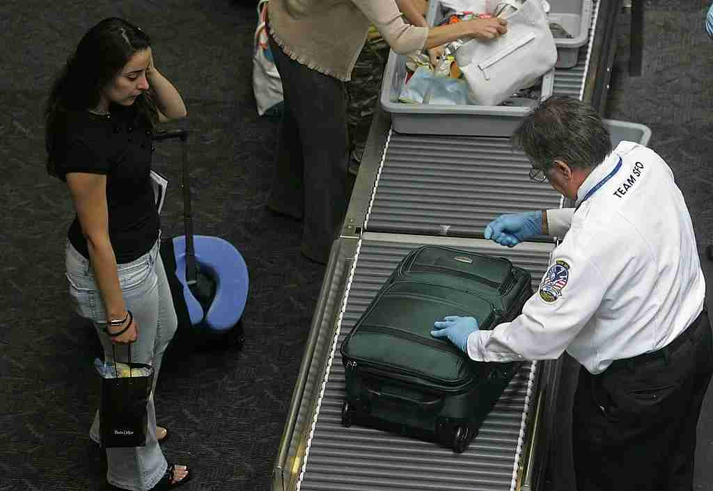 SAN FRANCISCO - AUGUST 10: A TSA employee searches the luggage of a United Airlines passenger at a security checkpoint at San Francisco International Airport August 10, 2006 in San Francisco, California. The Department of Homeland Security raised the terrorism alert to Red, the highest level, for commercial flights from Britain to the United States. The U.S. government banned all liquids and gels from flights effective immediately. (Photo by Justin Sullivan/Getty Images)