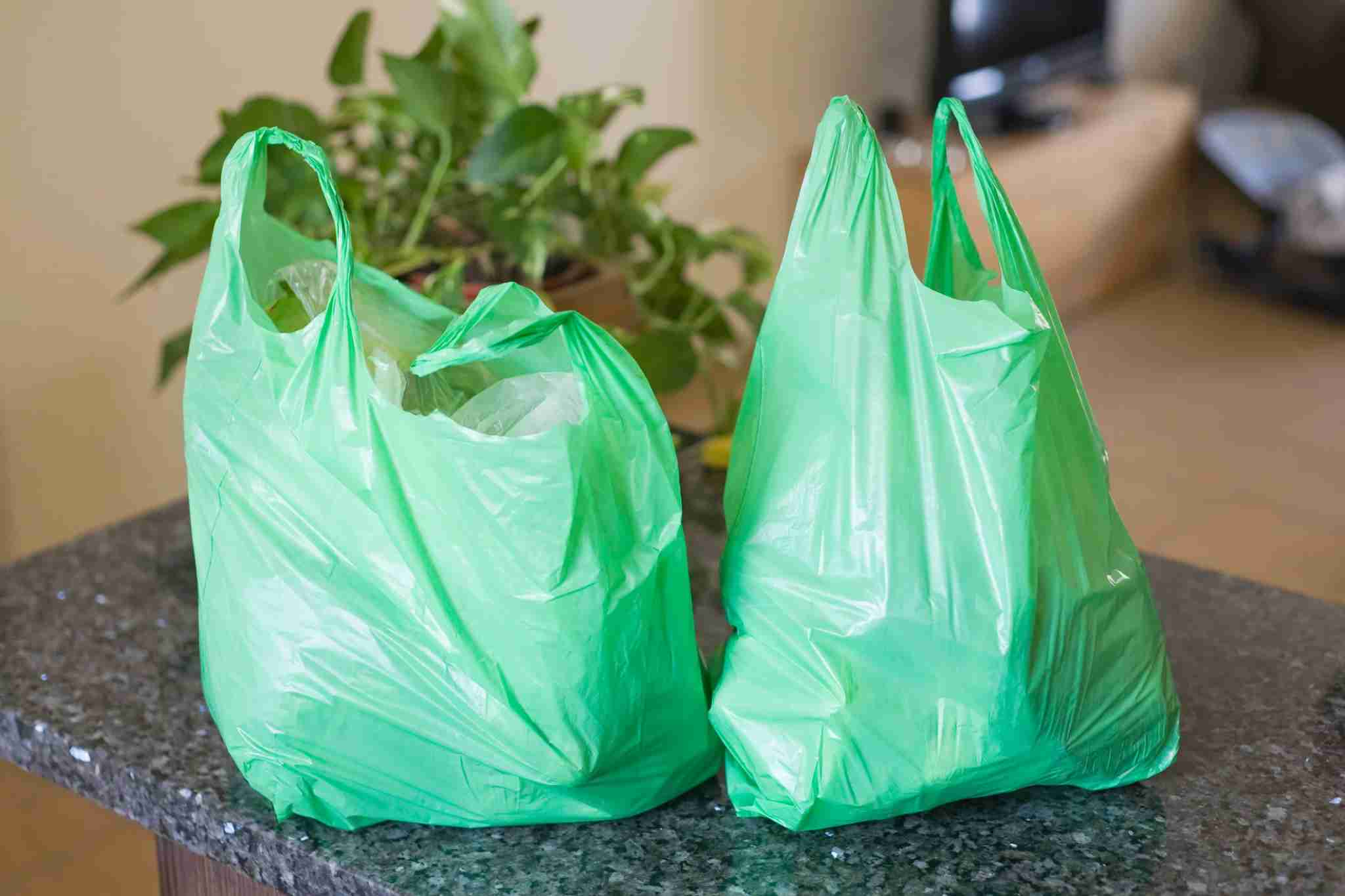 Green plastic bags on kitchen worktop.Alex Bramwell via Getty Images.