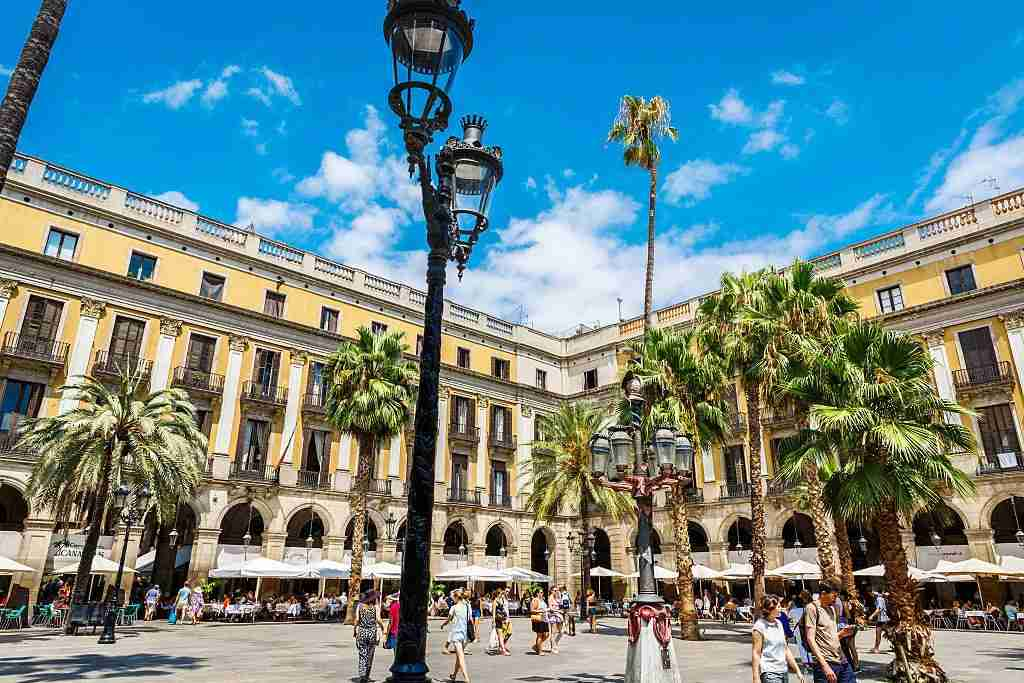 Escape Las Ramblas and duck into the nearby Plaça Reial for a breather. Image courtesy of Andia via Getty Images.