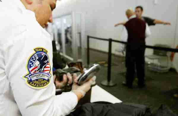 SAN FRANCISCO - AUGUST 5:  A Transportation Security Administration baggage screener inspects an electronics device as a man is screened in the background at the international terminal of San Francisco International Airport August 5, 2003 in San Francisco, California. The TSA told screeners today to pay close attention to cameras, laptop computers and cell phones, addressing a concern that terrorists could attempt to hide explosives in electronic devices.  (Photo by Justin Sullivan/Getty Images)