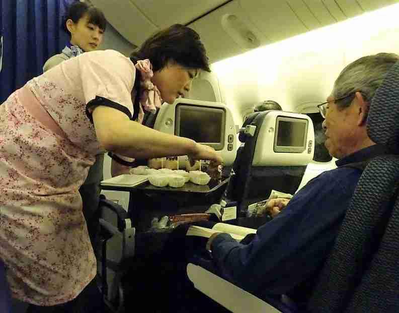 A flight attendant serves dessert.