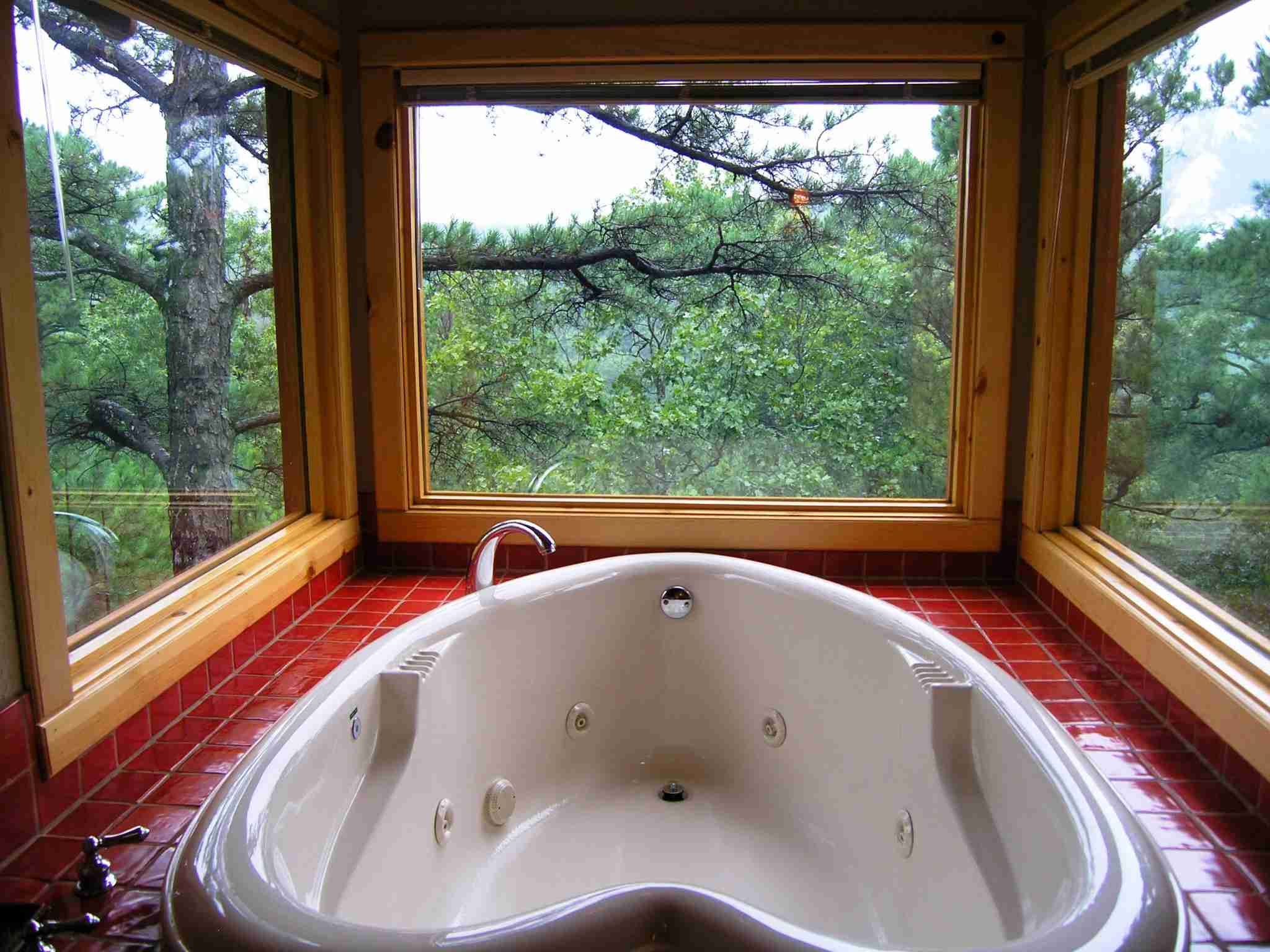 A double-size heart-shaped Jacuzzi is positioned in front three large windows. Photo courtesy of Laura at Tree House Cottages.