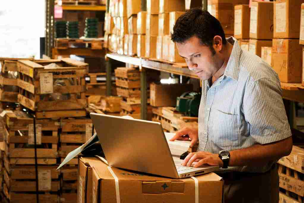 Hispanic manager working in warehouse going over inventory and shipping and receiving. (Photo by stevecoleimages/Getty Images)