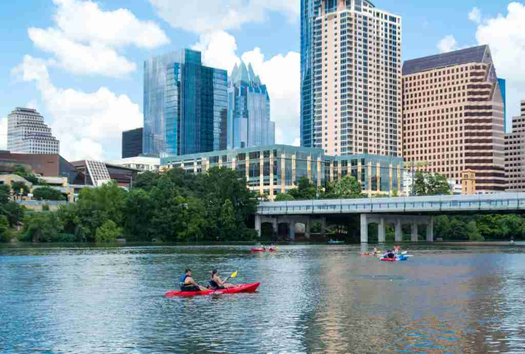 People canoeing on Lady Bird Lake in Austin with the Austin Skyline in the background. (Photo courtesy of Getty Images)