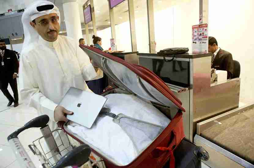 Kuwaiti social media activist Thamer al-Dakheel Bourashed puts his laptop inside his suitcase at Kuwait International Airport in Kuwait City before boarding a flight to the United States on March 23, 2017.Travellers across the Middle East have expressed frustration at a ban on large electronic devices for flights to the United States and Britain that has sparked confusion and speculation. From March 25, passengers on flights to the United States and Britain from major hubs in Turkey and the Arab world will have to check in any device larger than a smartphone, including laptops and tablets. / AFP PHOTO / Yasser Al-Zayyat (Photo credit should read YASSER AL-ZAYYAT/AFP/Getty Images)