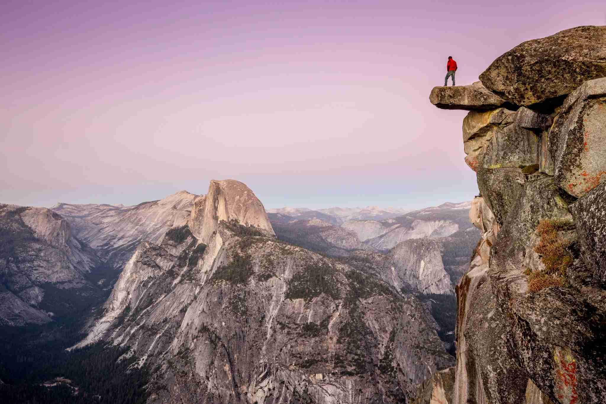 A fearless male hiker is standing on an overhanging rock at Glacier Point enjoying the breathtaking view towards famous Half Dome in beautiful post sunset twilight in summer, Yosemite National Park, California (Photo by bluejayphoto/Getty Images)