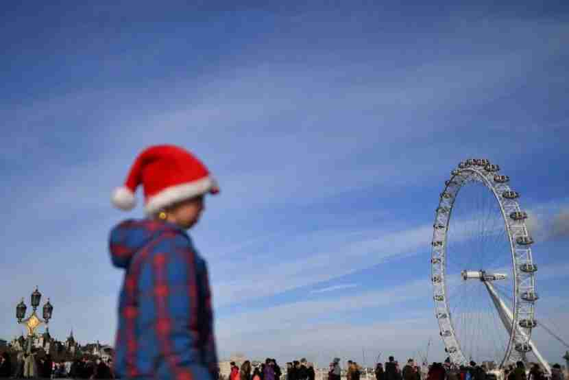 A girl in a santa hat is seen as people walk over Westminster bridge in London, on December 9, 2017 with the London Eye in the background. Britain and the European Union reached a historic deal on Brexit divorce terms on December 8, but Brussels swiftly warned that even harder talks lie ahead on a future relationship after the split. / AFP PHOTO / BEN STANSALL (Photo credit should read BEN STANSALL/AFP/Getty Images)