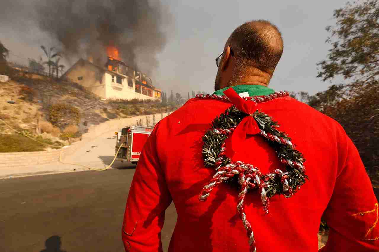 Wearing his Christmas garb Justin Ekback watches as Firefighters fight to save multi-million dollar homes along Cobblestone Drive near Foothill Road and North Victoria Avenue Tuesday midday after a fast-moving, wind-fueled wildfire swept into Ventura destroying many homes early Tuesday, burning over 45,000 acres, destroying homes and forcing 27,000 people to evacuate. (Photo by Al Seib/Los Angeles Times via Getty Images)