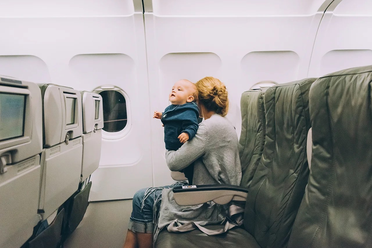 Woman traveling with her baby sitting in an airplane cabin. (Photo by Juanmonino/Getty Images)