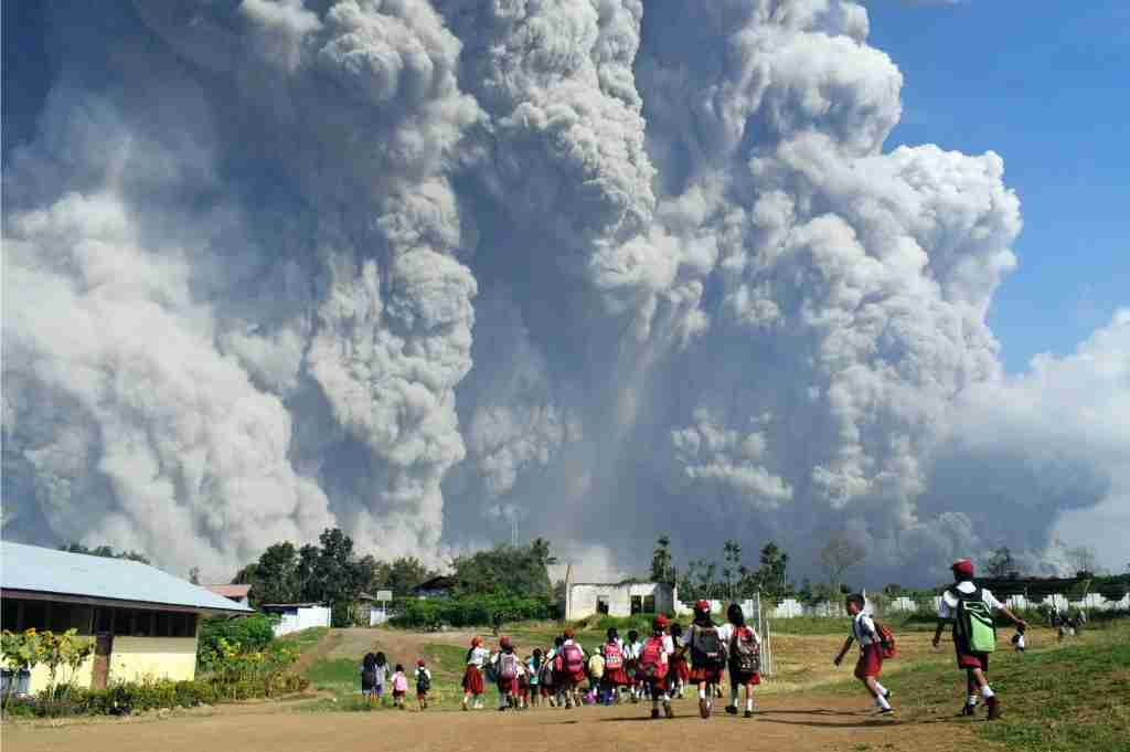 Indonesian schoolchildren walk together at Sipandak elementary school in Tiga Pancur village in Karo, North Sumatra on February 19, 2018, as thick volcanic ash from Mount Sinabung volcano rises into the air following another eruption.Sinabung roared back to life in 2010 for the first time in 400 years and has remained highly active since. (Photo by ANTO SEMBIRING/AFP/Getty Images)