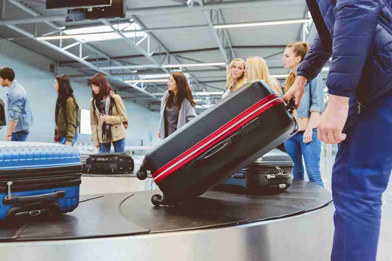 People waiting at baggage claim line terminal of the international airport. Airplane travelers waiting for luggage from a conveyor belt. (Photo by izusek/Getty Images)