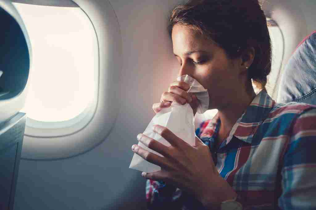 Young woman feeling bad during a flight and breathing in vomit bag. (Photo by martin-dm/Getty Images)