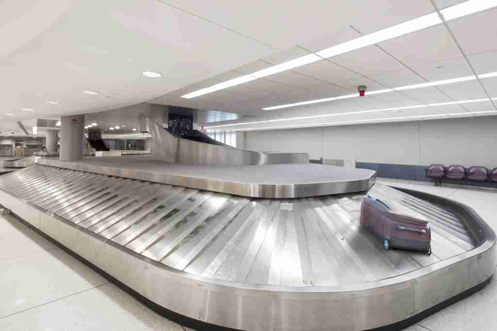 Suitcase on baggage claim carousel in airport (Photo by Spaces Images / Getty Images)
