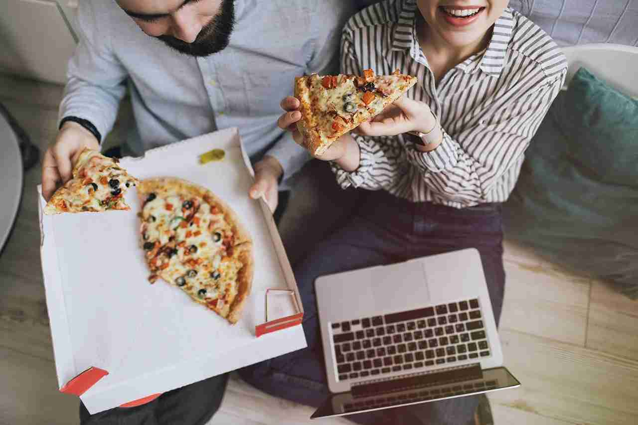 Young hipster male and female couple home eating pizza with laptop. (Photo by Katie_Martynova/Getty Images)