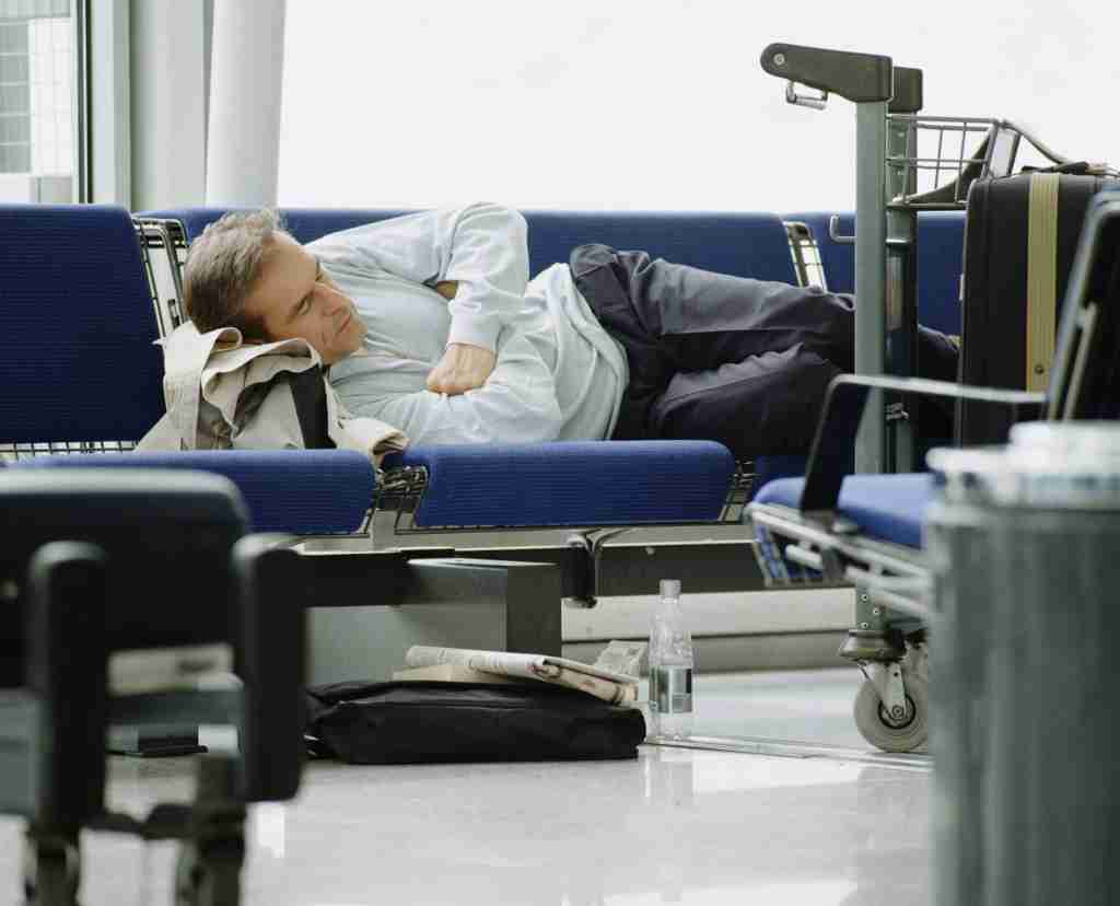 A passenger sleeps in Stansted Airport before the ban went into effect. Image by Getty Images.