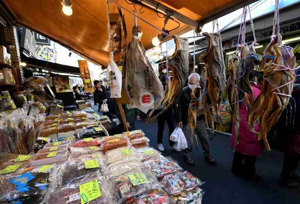 Year-end shoppers visit shops selling fresh and dried seafood outside Tsukiji fish market in Tokyo on December 28, 2017.People visited the shops to purchase food and supplies in preparation to celebrate New Year
